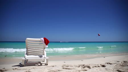 deck chairs : Santa Claus Hat on sunbed near tropical calm beach with turquoise caribbean sea water and white sand. Christmas vacation concept Stock Footage