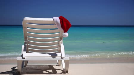 napágy : Santa Claus Hat on sunbed near tropical calm beach with turquoise caribbean sea water and white sand. Christmas vacation concept Stock mozgókép