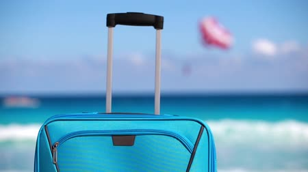 vacation destination : Closeup on handle of blue suitcase on tropical beach. Vacation concept