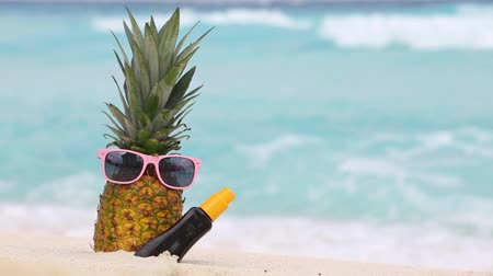 pleťová voda : Pineapple fruit in sunglasses and sunscreen protection cream bottle on sand against turquoise caribbean sea water. Tropical summer vacation concept