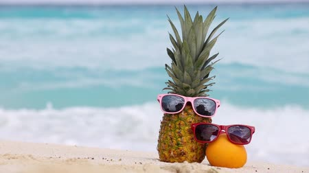 ananas : Pineapple and orange fruit in sunglasses and starfish on sand against turquoise caribbean sea water. Tropical summer vacation concept