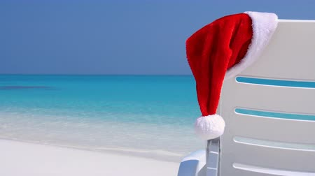 atol : Santa Claus Hat on sunbed near tropical calm beach with turquoise sea water and white sand