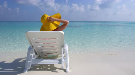 napágy : Woman in straw yellow sunhat sitting on a sunbed and looking to the sea