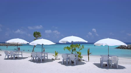 karibský : White sun umbrellas with tables and chairs at sandy beach