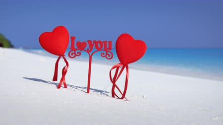 sand bank : Sign I love you and two red heart shapes on Maldivian beach Stock Footage
