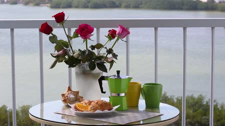 brew coffee : Delicious breakfast with coffee, fresh croissants and slice of orange fruit on hotels balcony Stock Footage