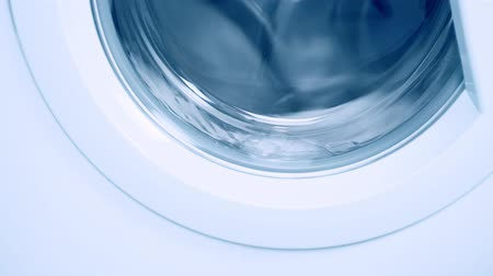 lavanderia : Washing machine washes white clothing and sheets. Cylinder spinning. Blue tone Stock Footage
