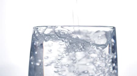 cold water : Pouring clean water into the glass. Closeup on white background Stock Footage