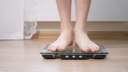 kaloryfer : Man step on digital glass scales to check his weight. Jumping after successful weighing Wideo