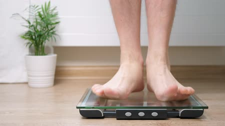 kaloryfer : Man step on digital glass scales to check his weight Wideo