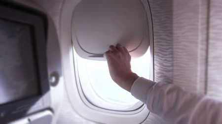 arms in the air : Close airplane window inside plane interior Stock Footage