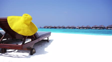 домик : Straw yellow sunhat on wooden sunbed at perfect sandy shore Стоковые видеозаписи
