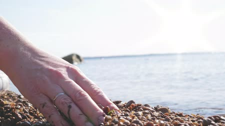 philosopher : Woman is pouring stones and sand through her fingers on Baltic gulf