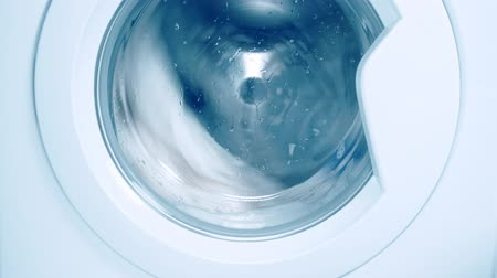 prát : Washing machine washes white clothing and sheets. Cylinder spinning. Blue tone Dostupné videozáznamy