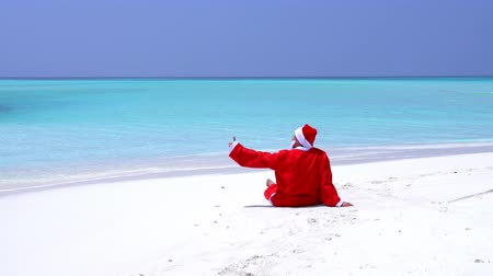 Man in Santa Claus Hat sitting and doing thumbs up on sandy beach