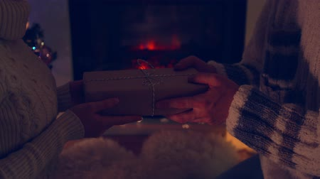 Man gives a new year present box to woman near fireplace