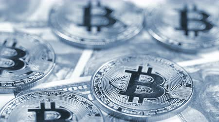 Rotating bitcoins on dollar banknotes background Stock Footage