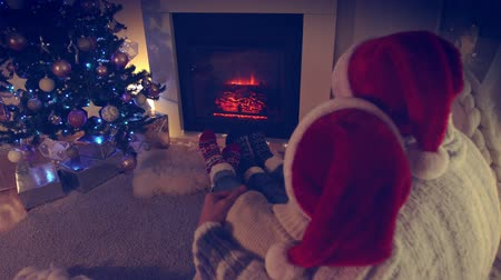 Couple sitting in Santa Hat near fireplace in living room