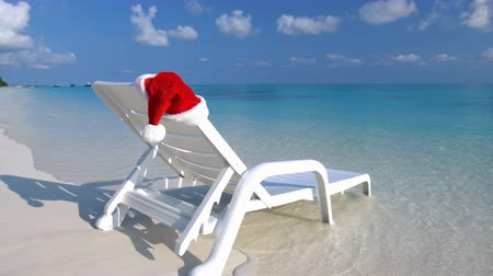 chaise longue : Santa Claus Hat on sunbed near tropical calm beach with turquoise sea water and white sand