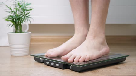 tartmak : Man step on digital glass scales to check his weight Stok Video