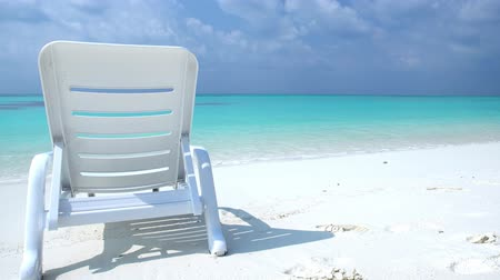 napágy : One sunbed on tropical calm shore with turquoise sea water and white sand Stock mozgókép