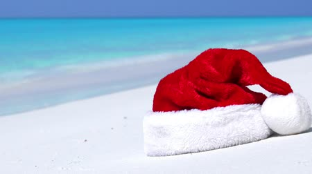 karácsonyi ajándék : Santa Claus hat on tropical sandy beach with calm waves Stock mozgókép
