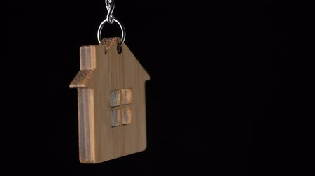 tuşları : Wooden key holder with house shape hanging and rotating on black background Stok Video