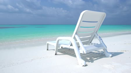chaise longue : One sunbed on tropical calm shore with turquoise sea water and white sand Stock Footage
