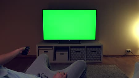 television set : Watching tv with green screen at home interior. Evening