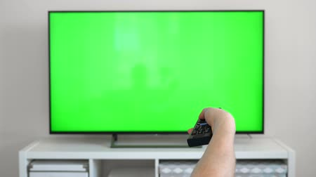 changing channel : Watching tv with green screen at home interior. Push buttons on remote. Changing channels on television