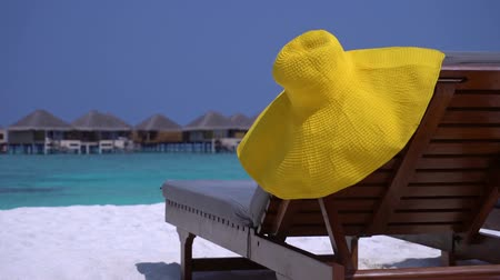 napágy : Yellow sunhat on sunbed at perfect sandy seashore with nobody