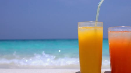 dois objetos : Two Cocktails in glass on white sandy beach with sea background Stock Footage