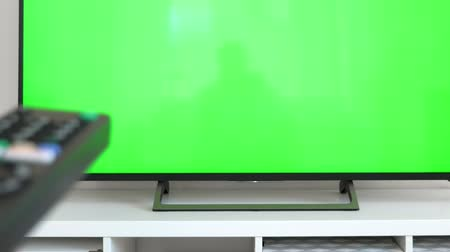 przycisk : Watching tv with green screen at home interior. Push buttons on remote. Changing channels on television