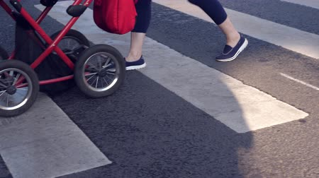 no traffic : Pedestrian crossing at city street with legs walking with baby buggy