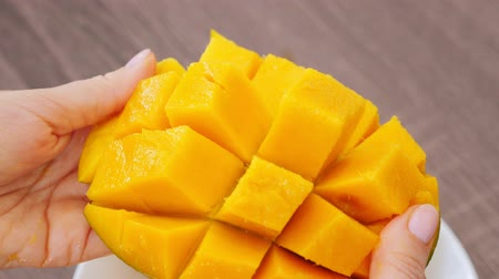 manga : Woman showing half cutted cubes slices mango Stock Footage
