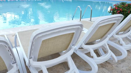 deck chairs : Sun beds and grab bars ladder at poolside