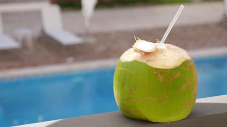 à beira da piscina : Coconut fruit with straw on balcony rail