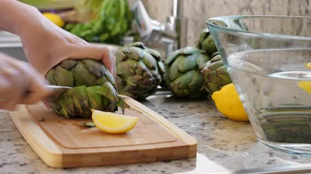 celý : Woman cut artichokes