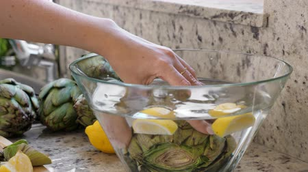 artisjok : Woman put artichokes in glass bowl