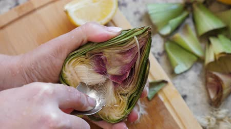 scrape : Woman cleaning heart of artichokes with spoon