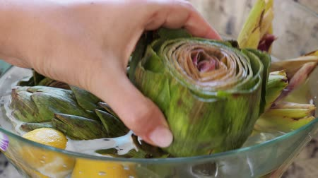 cardo : Woman take artichoke from glass bowl