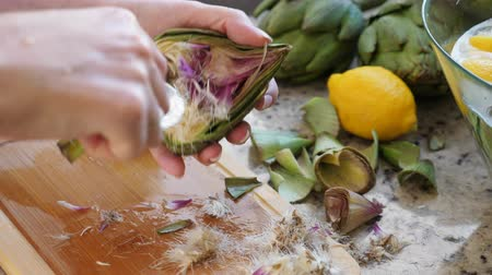 descamação : Woman cleaning heart of artichokes with spoon