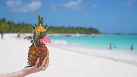 saona : Sweet pineapple cocktail in hand with caribbean beach background