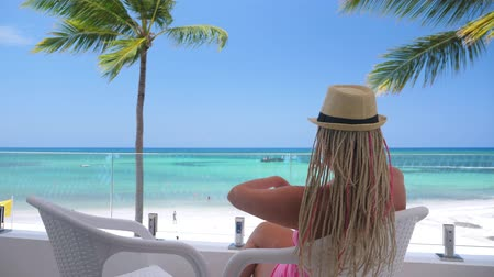 veranda : Happy Tourist woman in summer hat sitting and enjoy sea view at balcony
