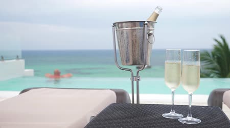 флейты : Cold champagne bottle in ice bucket and two glasses of sparkling wine on table Стоковые видеозаписи
