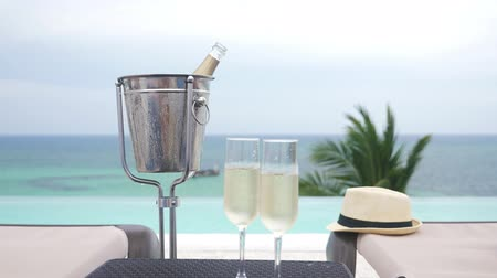champagne pool : Cold champagne bottle in ice bucket and two glasses of sparkling wine on table Stock Footage