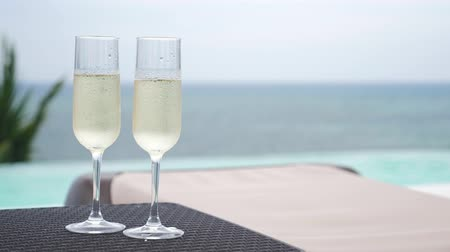 champagne flute : Cold champagne in two glasses of sparkling wine on rattan table