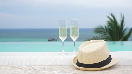 флейты : Cold champagne in two glasses of sparkling wine and hat near swimming pool