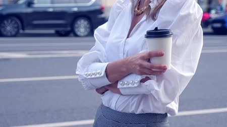 elvihető : Woman in sunglasses with take away coffee catching a taxi in the city Stock mozgókép