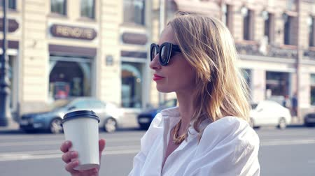 навынос : Woman in sunglasses with take away coffee catching a taxi in the city Стоковые видеозаписи
